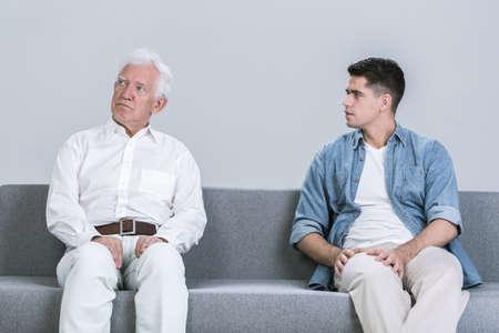 senior adult man: Senior man and his adult son sitting on a sofa