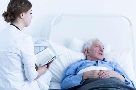 hospice: Female nurse reading book to senior patient in hospice
