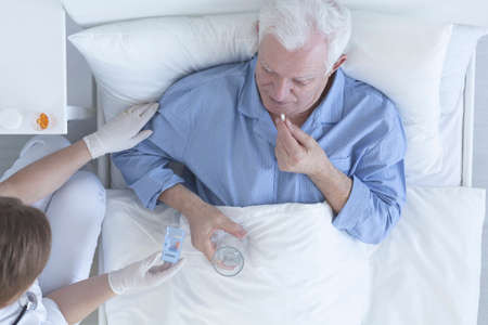 swallowing: Patient lying in hospitl bed taking pill with glass of water