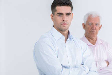 senior adult man: Handsome adult man in the background his senior father, light background