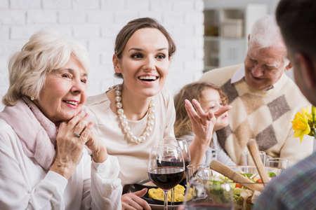 Multi-generational family talking and enjoying dinner together Foto de archivo