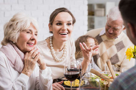 Multi-generational family talking and enjoying dinner together Stock fotó