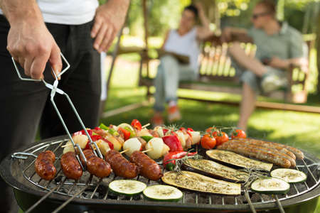 delicious food: Shot of a group of friends having a barbecue outside