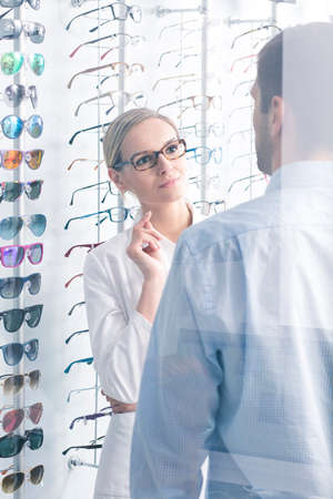 optometrist: Attractive optometrist and man choosing a new frames Stock Photo
