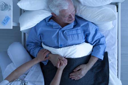 persona enferma: Médico o enfermera de la mano del paciente de sexo masculino mayor acostado en la cama de cuidados paliativos Foto de archivo