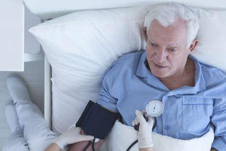 sphygmomanometer: Nurse using a sphygmomanometer to measure senior patients blood pressure Stock Photo