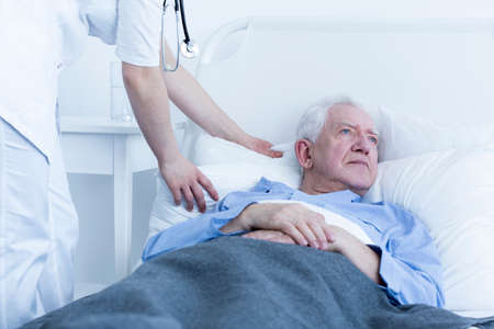 hospice: Nurse fluffing pillow of elderly male patient at hospice