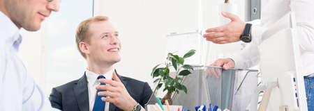 accepting: Panoramic picture of a very happy young office worker accepting praises from a man standing by his desk