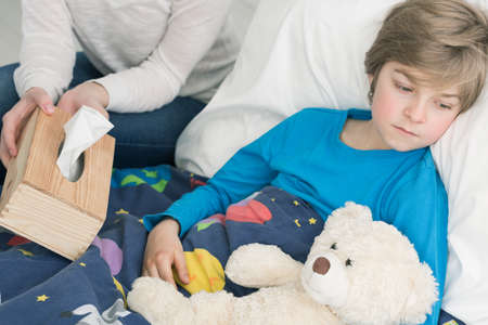 sick teddy bear: Shot of a sad sick little boy laying on a bed with his teddy bear Stock Photo