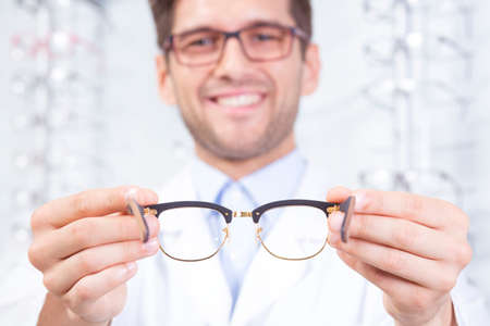 optician: Content man optician holding a new pair of glasses Stock Photo