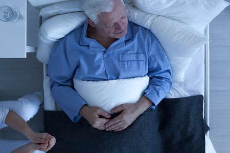 Ancianos enfermos al paciente acostado en la cama de hospital de sexo masculino
