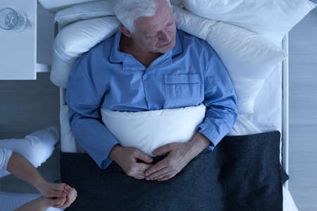 hospital patient: Sick elderly male patient lying in hospital bed Stock Photo