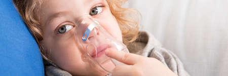 asma: niño acostado en el sofá y que tiene la medicina de inhalación Foto de archivo