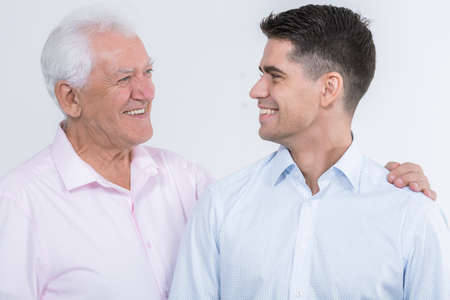 elderly adults: Happy mature father and his adult son looking at each other with love, light background Stock Photo