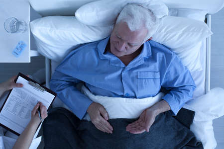 hospital notes: Doctor taking notes from senior man patient lying in hospital bed Stock Photo