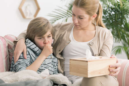 niños malos: Disparo de un niño pequeño tos y su madre sentada junto a él