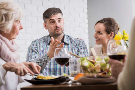 anecdote: Man sitting and discussing with his family at the table