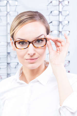 trying: Beautiful woman trying on new pair of glasses Stock Photo