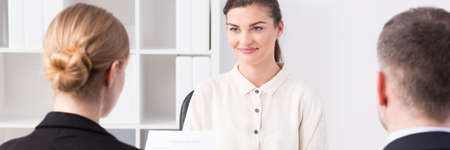 supervisores: Sonrió y trabajador de confianza de las mujeres está sentado en frente de sus supervisores