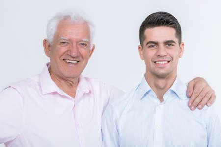 Senior man lachend met zijn hand op een jonge man arm, lichte achtergrond Stockfoto
