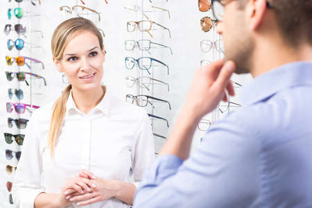 optician: Professional, beautiful optician and man standing in eyewear store