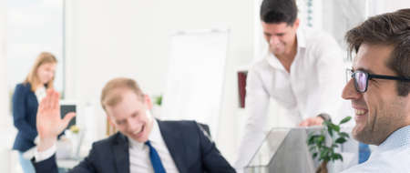 workmates: Blurry panoramic image of laughing workmates in a very bright office space Stock Photo