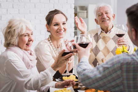 food and wine: Happy family making a toast with red wine at dinner
