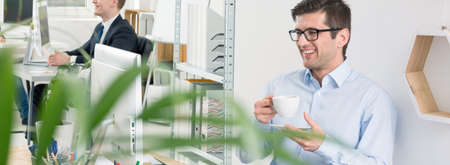 graphic design: Panoramic picture of a cheerful graphic designer holding a cup of coffee in fron of his computer