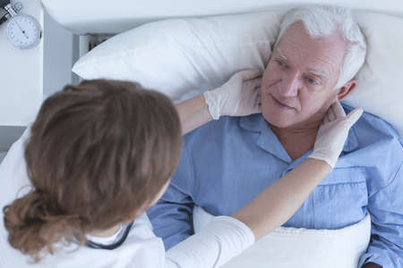 hospice: Doctor examing hospice elderly male patient lying in bed