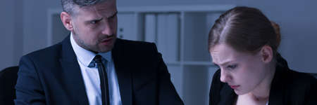 intimidated: Unhappy boss looks at his intimidated female worker Stock Photo