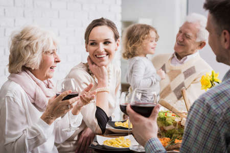 Happy multi-generational family gathering during holidays at the table Stock Photo - 58409040