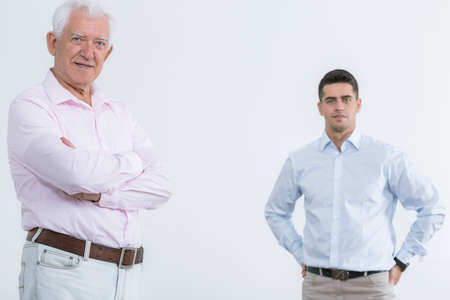 sons and grandsons: Proud senior man smiling and handsome young man, light background Stock Photo