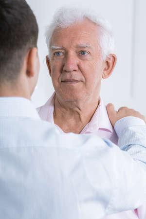senior adult man: Adult man rearview holding his arm on senior mans arm Stock Photo