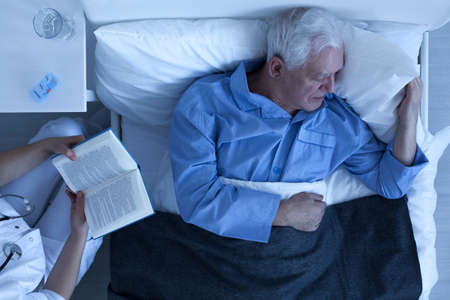 hospital patient: Nurse reading for lonely and suffering patient in hospital room Stock Photo