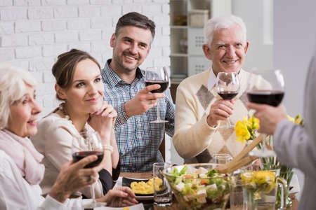 Gelukkige familie die een toast met rode wijn aan tafel
