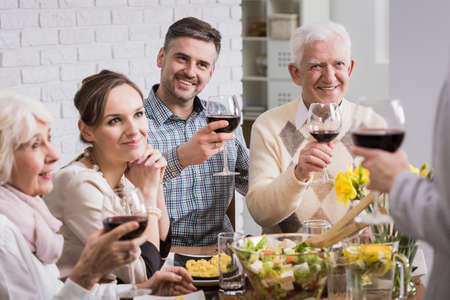 Happy family making a toast with red wine at the table