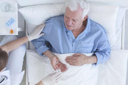 hospital patient: Nurse giving sick senior male patient tablets at hospital