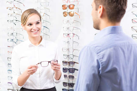 optical: Beautiful optometrist holding pair of glasses, talking with client