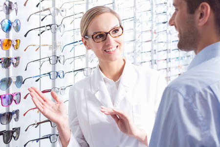 optician: Beautiful optician and man choosing a new pair of glasses