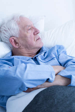 hospital patient: Pensive elderly male patient lying in hospital or hospice bed