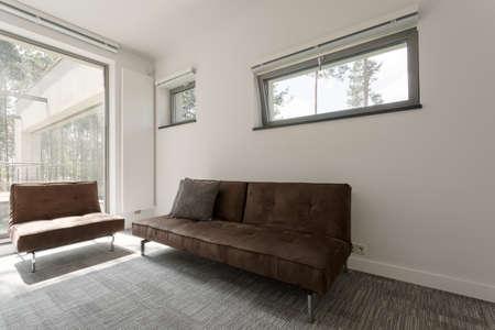 spacious: Shot of a brown sofa in a spacious modern house