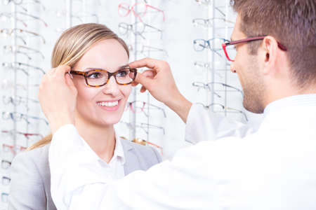 Optometrist putting a pair of glasses on a patient Imagens - 58409089