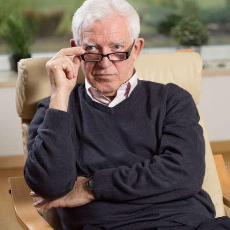 portrait man: Portrait of senior psychotherapist sitting on armchair Stock Photo