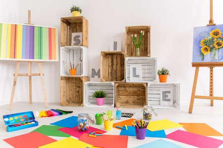 paleta de pintor: sala blanca espaciosa con dos caballetes con imágenes y estantes hechos de cajas de madera junto a la pared. En el suelo las hojas de colores de papel