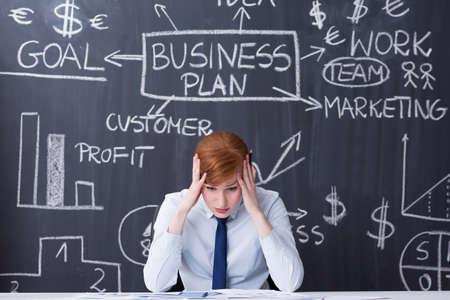 pensamiento estrategico: la mujer del jengibre agotado sentado junto a la mesa, sosteniendo su cabeza, plan de negocios dibujado en una pizarra en el fondo