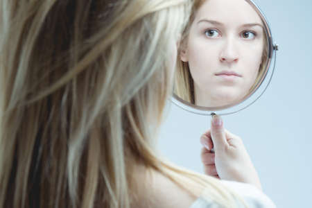 Reflection of woman with mental problem holding mirror. Stock Photo