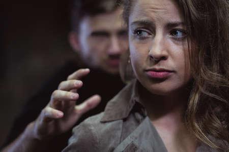 Schot van het gezicht van een vrouw bang en een vreemde man die achter haar
