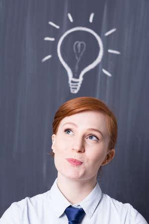 pensamiento estrategico: J�venes de negocios de jengibre con una bombilla encima de la cabeza, pizarra en el fondo