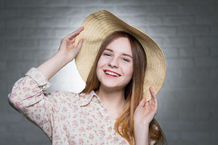 express feelings: Happy young beautiful girl prepared for summer. Wearing shirt in flowers and straw hat