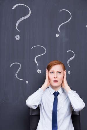 pensamiento estrategico: Mujer tensionada jengibre sosteniendo su cabeza, signos de interrogación en la pizarra en el fondo